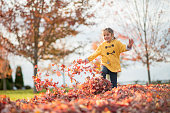 A cute little girl is running thought a pile of dried leaves on a sunny autumn day.