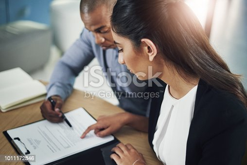 Shot of two businesspeople going through some paperwork in an office