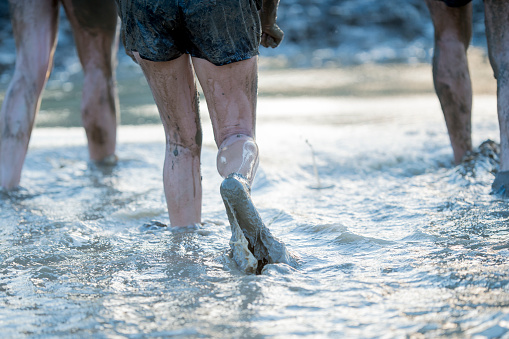 687723318 istock photo Running Through the Mud and Water 687722952