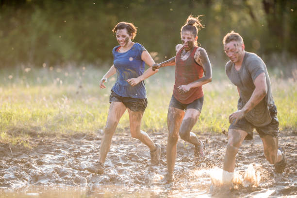 Running Through The Mud Two women and a man are participating in a mud run. They are running through muddy water and getting dirty. mud run stock pictures, royalty-free photos & images