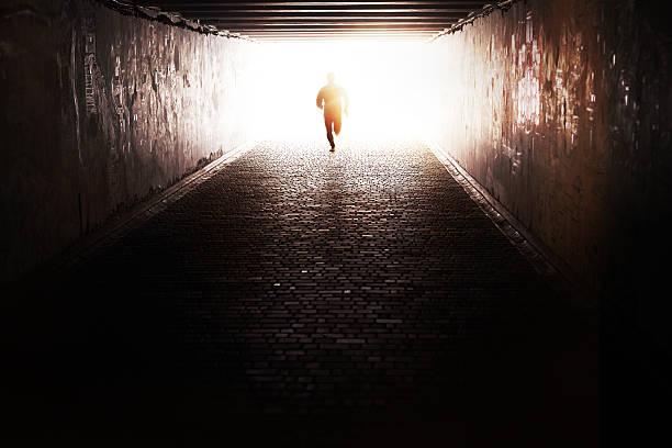 laufen durch den tunnel - alles hinter sich lassen stock-fotos und bilder