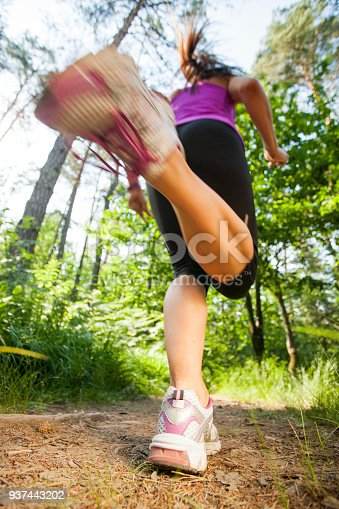 Female runner in fast motion running over the camera in the forest.