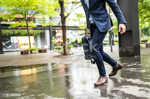 Unrecognizable businessman running to work, low angle view of his pants and shoes on wet city street