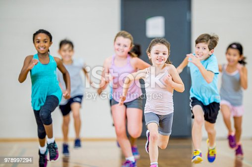 A group of children are exercising inside of a gym at school. They are having fun running towards the camera.