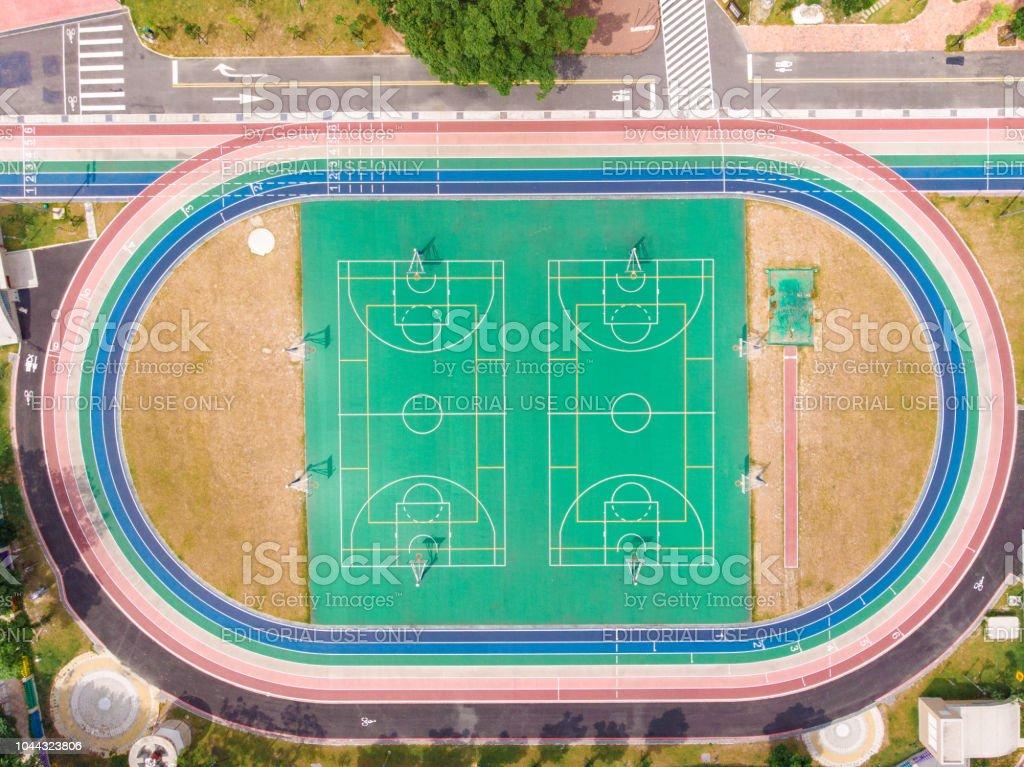 Pista de corrida e basquete tribunal no estádio, cor multicolor, alto ângulo vista pela sonda. - foto de acervo