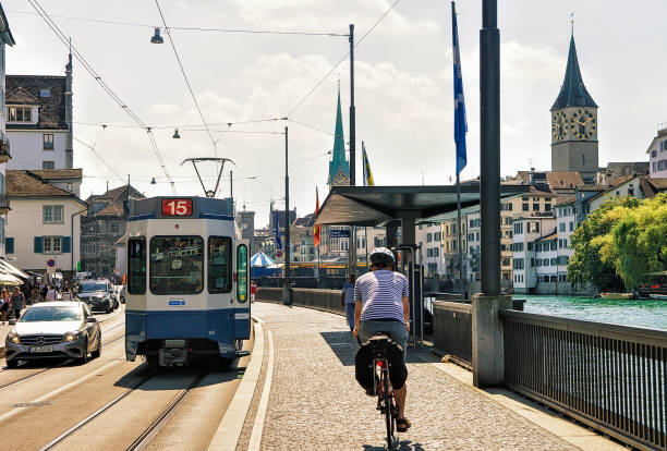 Running Tram and man riding bicycle at Limmatquai in Zurich Zurich, Switzerland - September 2, 2016: Running Tram and man riding a bicycle at Limmatquai. Saint Peter Church and Fraumunster Church in the city center of Zurich, in Switzerland. limmat river stock pictures, royalty-free photos & images