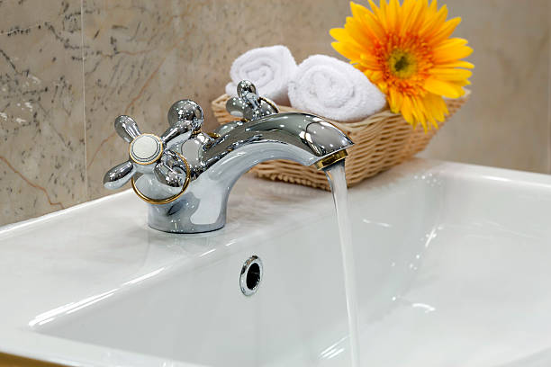 Running water bathroom faucet with basket nearby stock photo