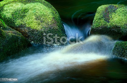 Running water in a stream between two moss covered rocks, UK