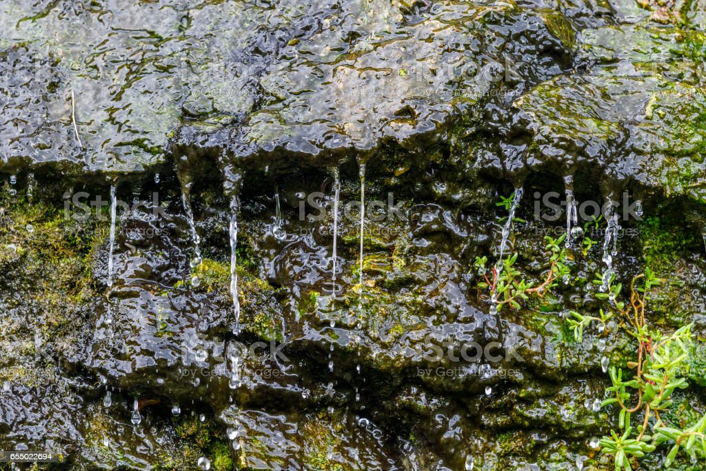 Running water on a rock wall stock photo