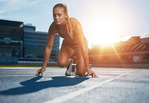 Running with determination Fit and confident woman in starting position ready for running. Female athlete about to start a sprint looking away. Bright sunlight from behind. track starting block stock pictures, royalty-free photos & images