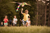 Carefree boy having fun while running with a kite at the park. His friends are in the background. Copy space.