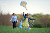 Sweet little girl running with a kite in front of his mother and sister. Female part of the family spending time in fun and games outdoor.