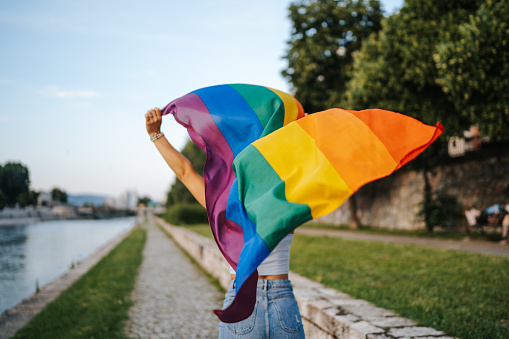 Young  lesbian woman with rainbow flag running on city quay