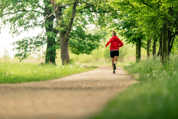 Running woman, enjoying summer day in park stock photo