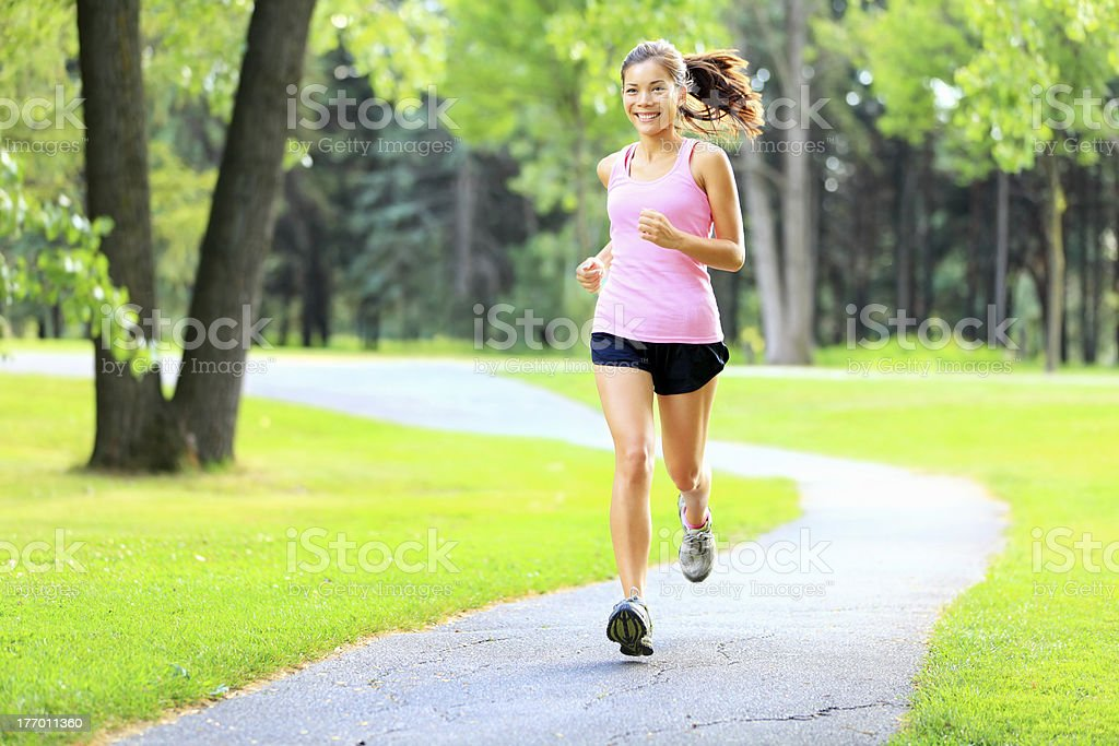 Running woman in park stock photo