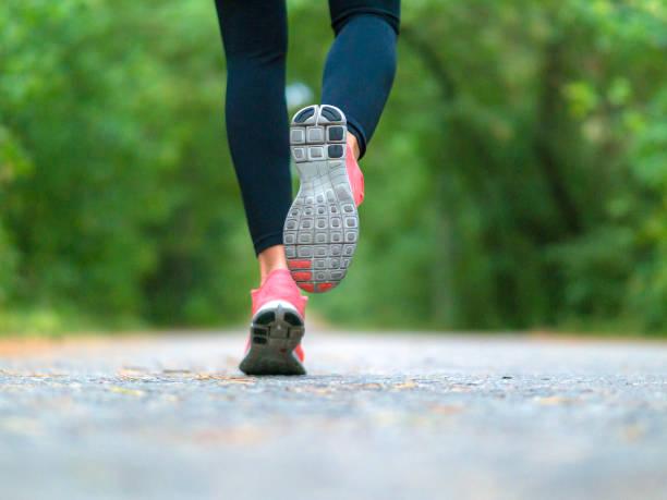 laufende frau im wald. nahaufnahme von sneakers. - joggerin stock-fotos und bilder