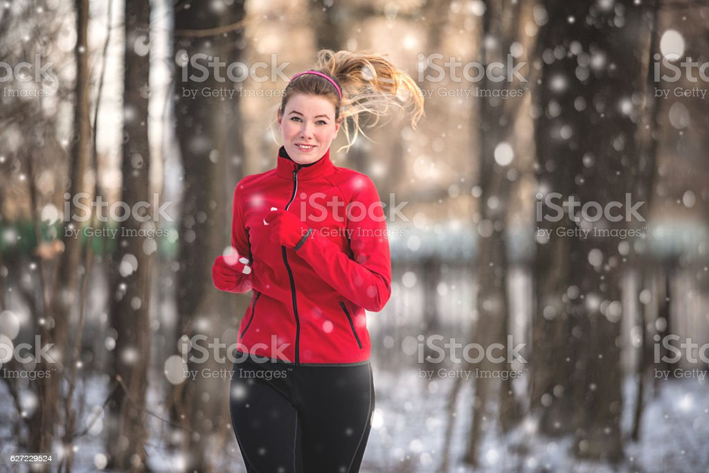 Running woman in winter forest stock photo