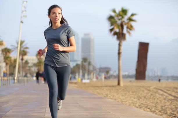 Running woman jogging Barcelona Beach Barceloneta stock photo