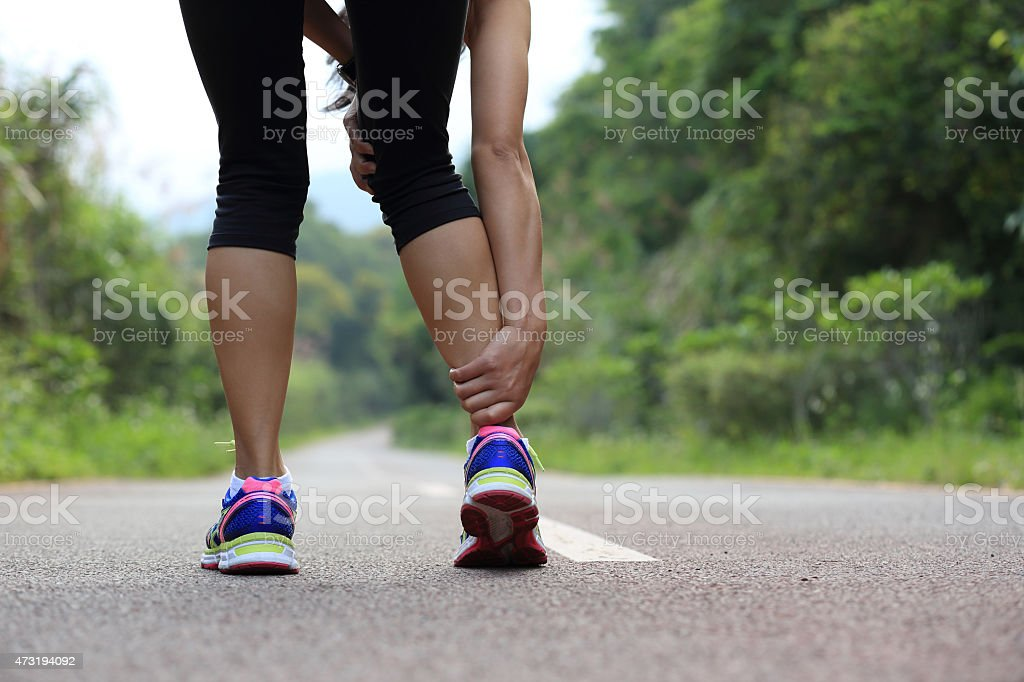 Running woman on highway holding her injured leg stock photo