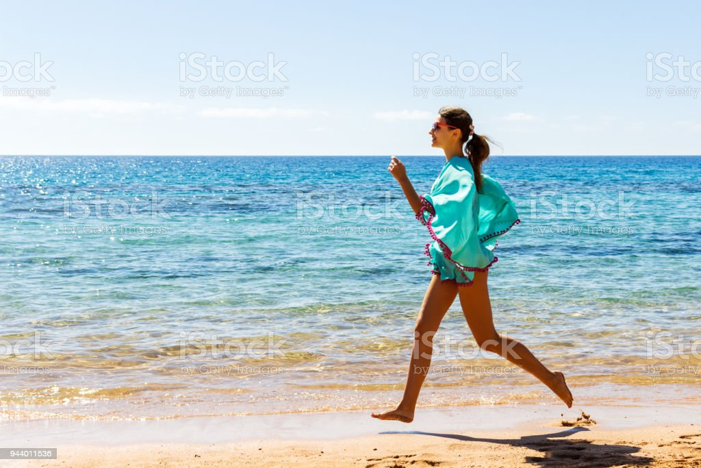 Running woman on the bech. Female runner jogging during outdoor workout on beach stock photo