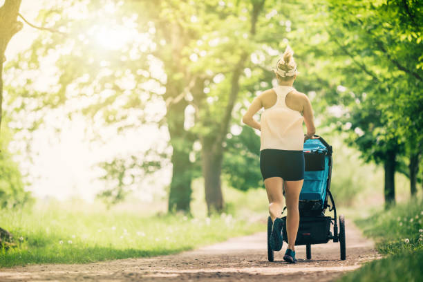 Running woman with baby stroller enjoying summer in park stock photo