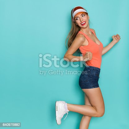 Beautiful woman in orange shirt, jeans shorts, white sneakers and sun visor standing on one leg, looking over shoulder and smiling. Three quarter length studio shot on teal background.