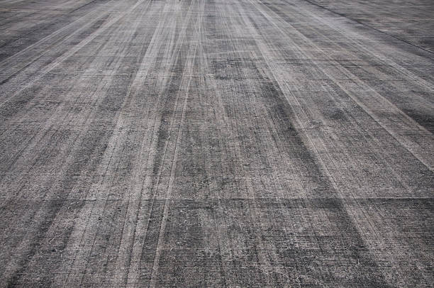 Runway Background Rubber tyre markings on a tarmac runway. tire track stock pictures, royalty-free photos & images