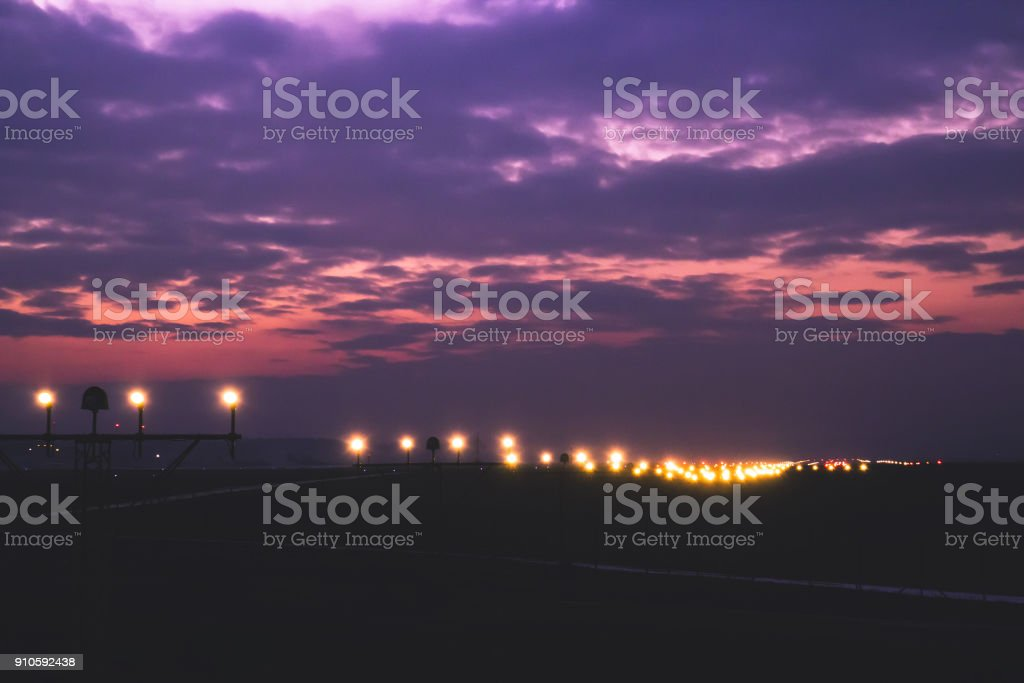 Runway Lighting Systems  in sunsed  bakground, red and purple fantastic dramatic skies stock photo