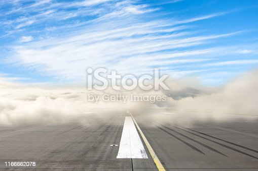 Runway road wrapped in dense low fog, clear blue sky from above. The concept of bad weather at the airport, the delay in the schedule of transport