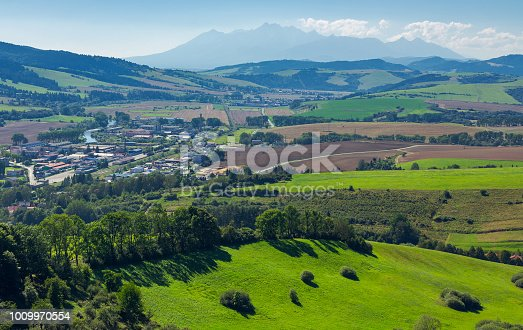 rural area around the town. grassy hill and agricultural fields. High tatra mountain ridge in the distance. view from the top of a castle tower