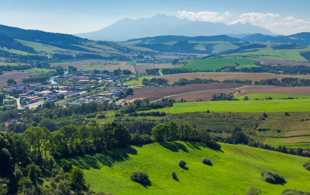rural area around the town rural area around the town. grassy hill and agricultural fields. High tatra mountain ridge in the distance. view from the top of a castle tower surrounding stock pictures, royalty-free photos & images