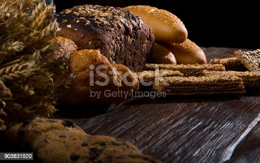 istock Rural bread and wheat on an old antique wooden table, still life 903831520