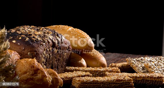 istock Rural bread and wheat on an old antique wooden table, still life 903831576