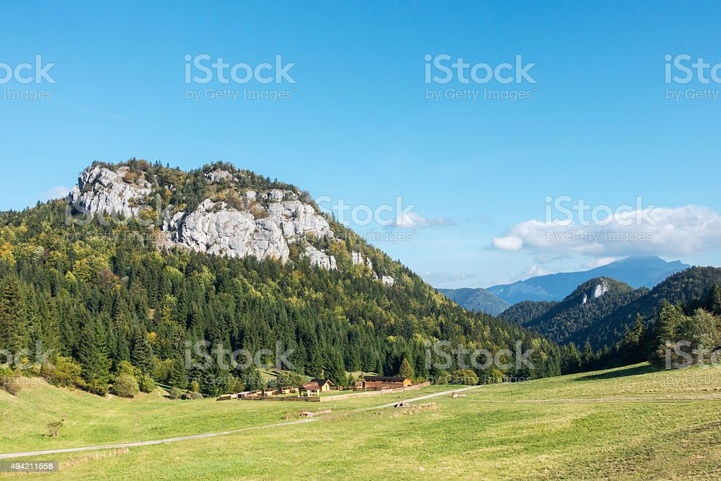 Rural chalet under amazing limestone rock hill stock photo