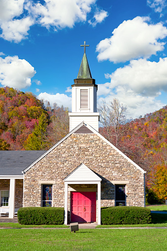 A small rural Christian church building on a bright Sunday morning.