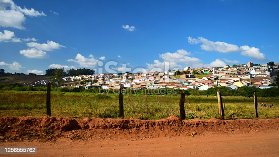 Part of the rural city of Monte Belo seen from a dirt road, in the state of Minas Gerais state, Brazil. The dry yellowish green pasture on it is due to the lack of rain during this period of the year. The skies are beautiful blue with few clouds in it during winter.