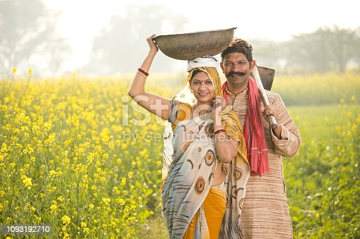 istock Rural couple with iron pan and hoe in agricultural field 1093192710