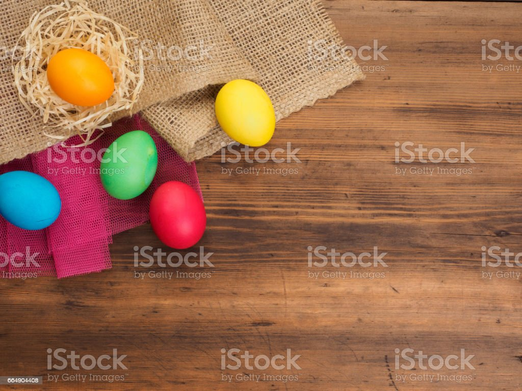 Rural eco background with colored chicken egg and straw on the background of burlap and old wooden planks. The view from the top. Creative background for Easter cards foto stock royalty-free