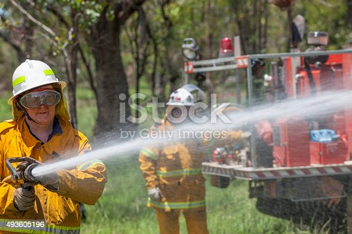A female rural fire fighter with hose and fire truck. She is dressed in protective clothing.