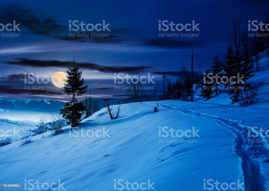 rural footpath through snowy hillside at night stock photo