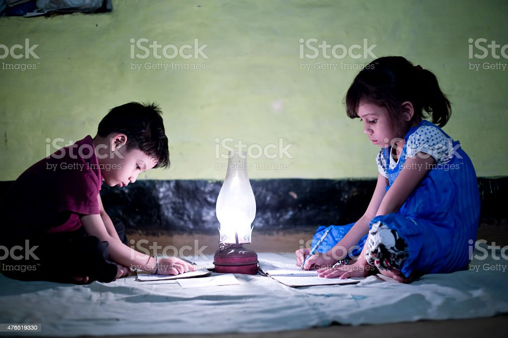 Rural girl and boy studying in lantern stock photo