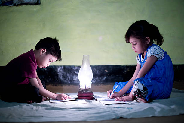 rural girl and boy studying in lantern - village stock photos and pictures