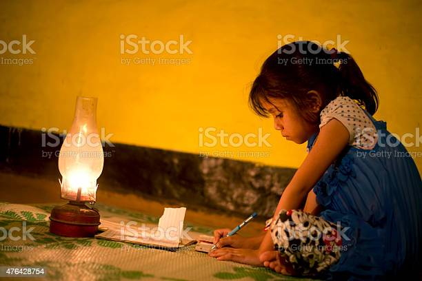 Village Girl studying in lighting lamp