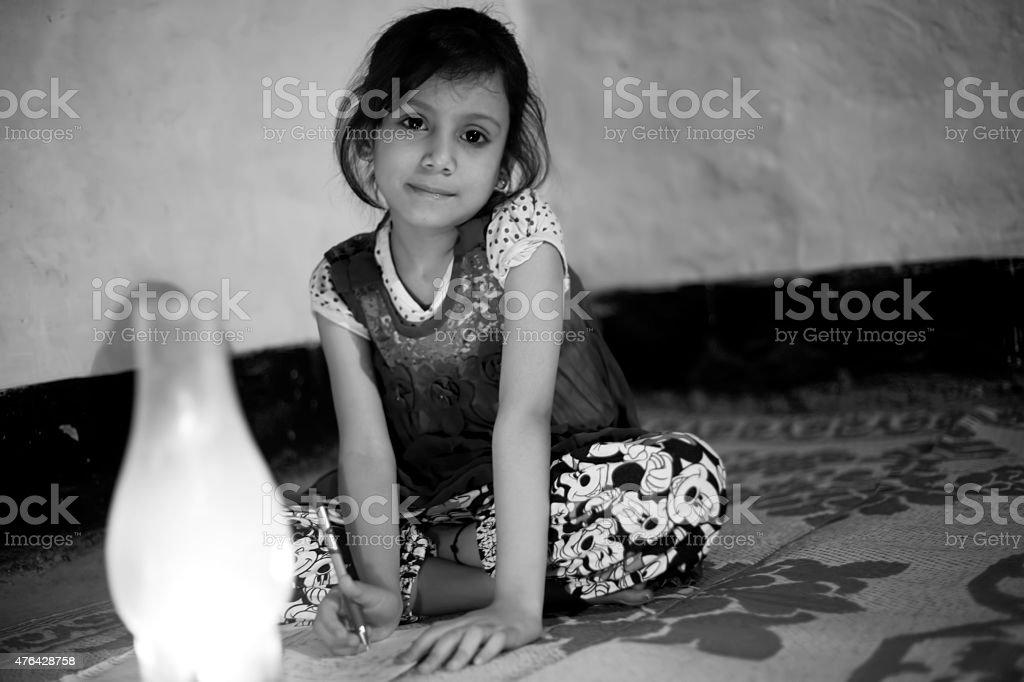 Rural girl studying in lantern stock photo