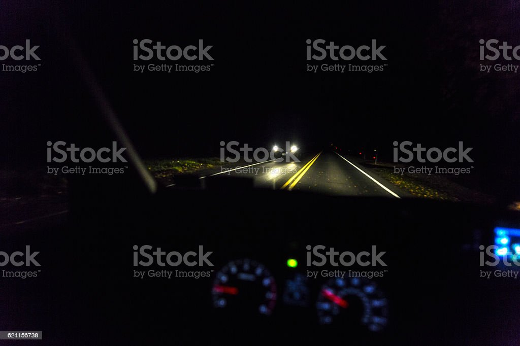 Rural Highway Night Time Approaching Vehicle Headlights stock photo