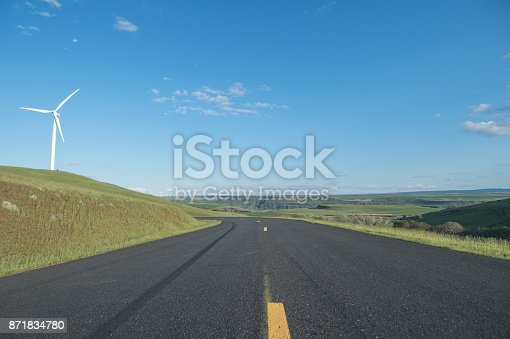istock Rural highway surrounded by turbine farm and rolling hills of grass. Blue sky and ridges and plateaus are off in the distance. 871834780