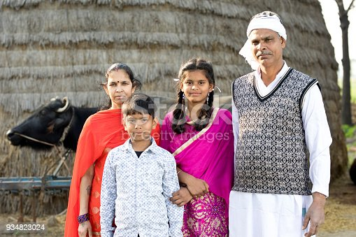 Rural Indian family posing in front of buffalo