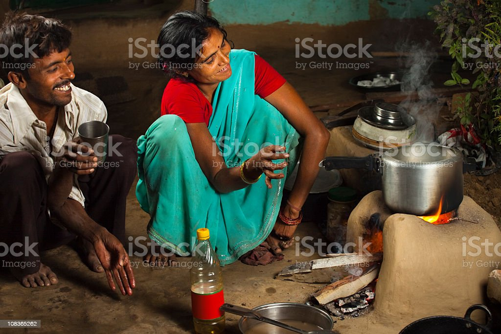 Rural, Indian husband and wife cooking dinner on clay stove royalty-free stock photo
