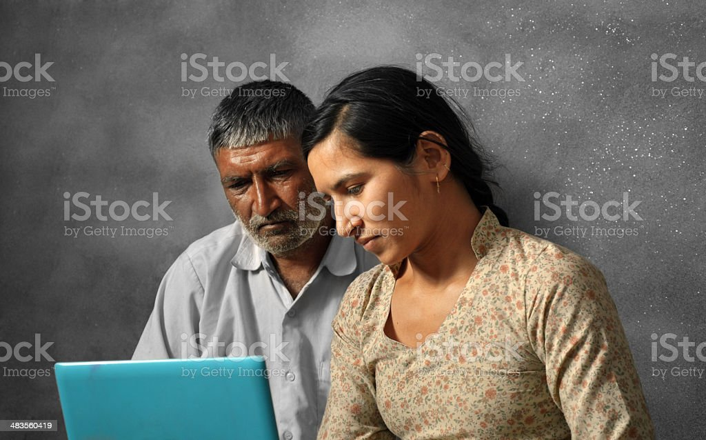 Rural Indian Man Using Laptop with his Daughter royalty-free stock photo