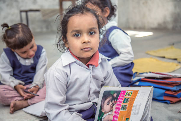 Rural Indian Pre school Kids sitting on the floor of their classroom. Local school kids sitting on the floor of his classroom and looking at camera, he is having his notebook and pencil . developing countries stock pictures, royalty-free photos & images